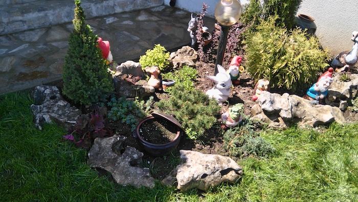 kleie gartenfiguren mit zwergen und weißen hasen und grauen steinen, einem grünen rasen und lampen, einen steingarten anlegen
