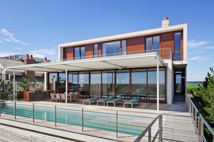 schönes eckiges design von einem modernen haus, grundriss haus, pool im garten, liegestühle, sommer