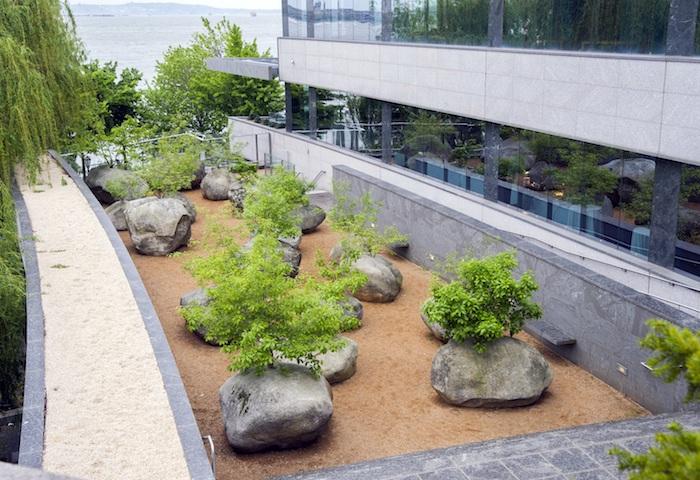 haus mit kleinem garten mit großen grauen steinen, steingarten bilder und ideen, ein steingarten mkt bäumen mit grünen blättern