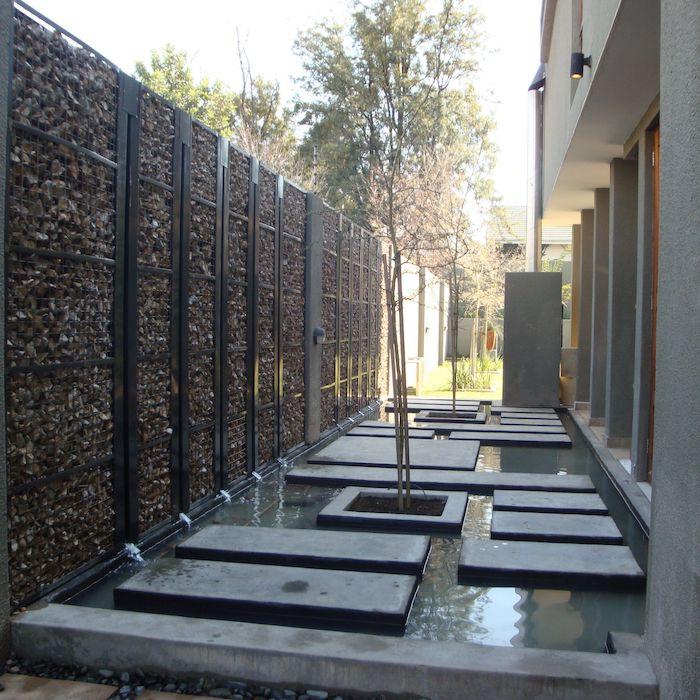 graues haus mit pool im garten mit bäumen und einem sichtschutz aus gabionen mit vielen kleinen natursteinen