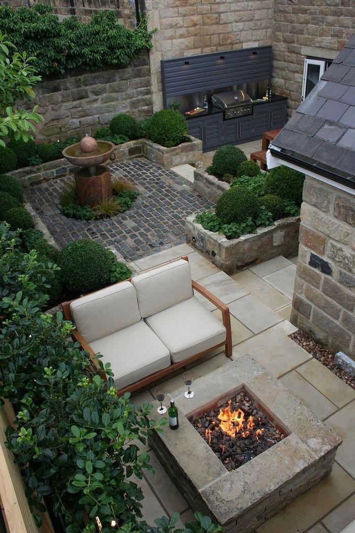 ein haus mit kleinem garten mkit sofas und weißen kissen und einem kleinen kamin mit feuer und sichtschutz aus grünen pflanzen