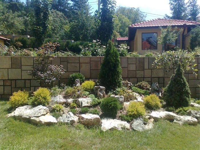 gartenzaus aus gelben fliesen und grünen pflanzen, ein haus mit grünem rasen und einem kleinen steingarten mit weißen steinen und grünen sukkulenten