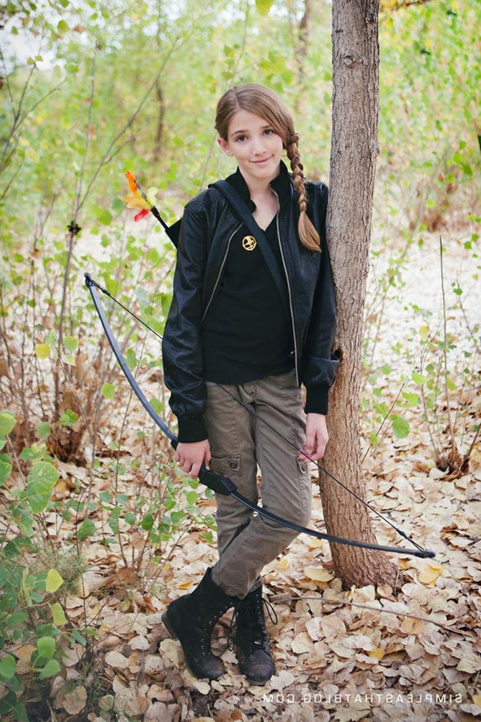 eine junge Katniss Everdeen mit Boden und Pfeile, im Wald, Mädchen mit Zopf und Brösche