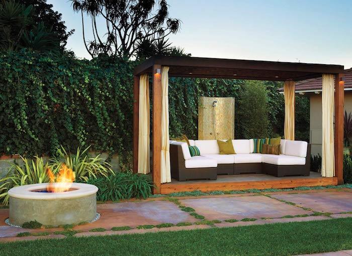 kleiner garten mit einem kamin und einem gartenweg und sofas mit weißen und grünen kleinen kissen und ein zaum aus grünen sichtschutz pflanzen