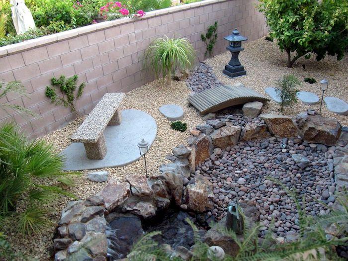 ein gartenzaun und kleiner garten mit gartenteich und steinen und grünen pflanzen, eine bank aus steinen, gartenteich anlegen