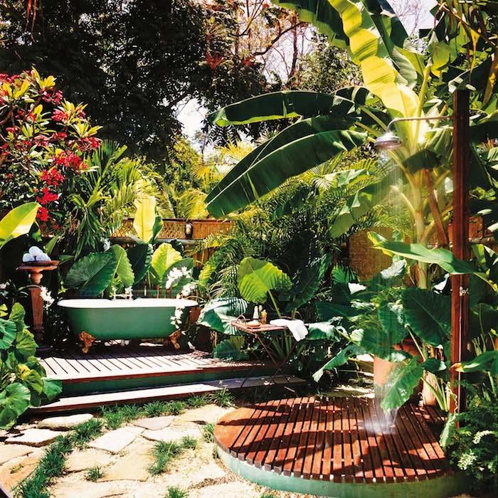 viele grüne palmen mit grünen blättern und rote blumen, ein garten mit kleiner grünen badewanne und dusche, sichtschutz für gartendusche aus exotischen pflanzen