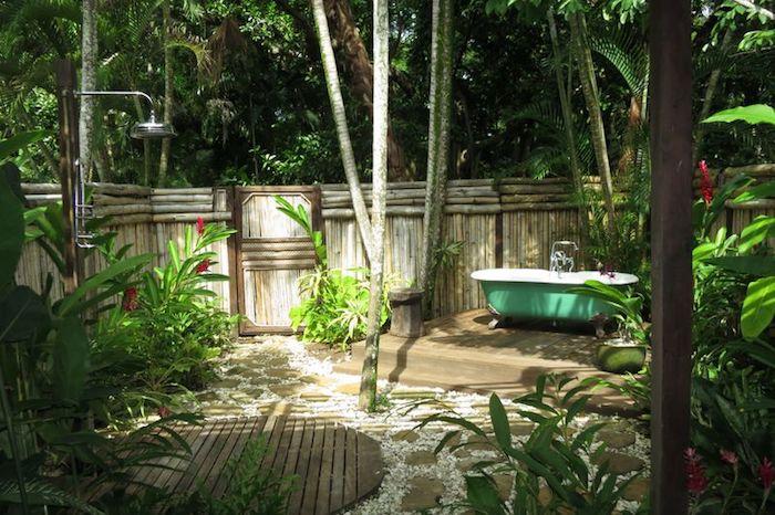 eone kleine grüne badewanne in einem garten mit einem boden aus holz und mit vielen grünen pflanzen mit grünen blättern
