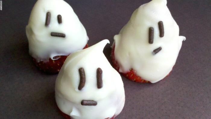 drei Erdbeeren wie Gespenster, mit weißer Creme und Schokoladestreusel, Halloween Menü