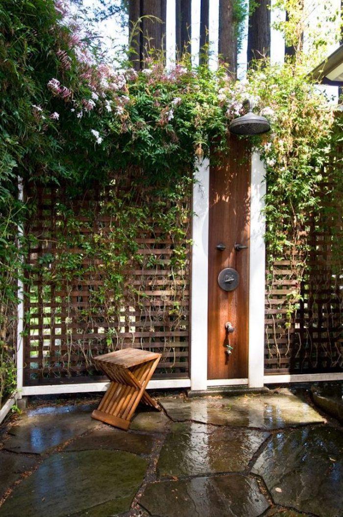 kleiner brauner stuhl aus holz und eine wand aus kletterpflanzen und pinken blumen, sichtschutz für eine gartendusche holz