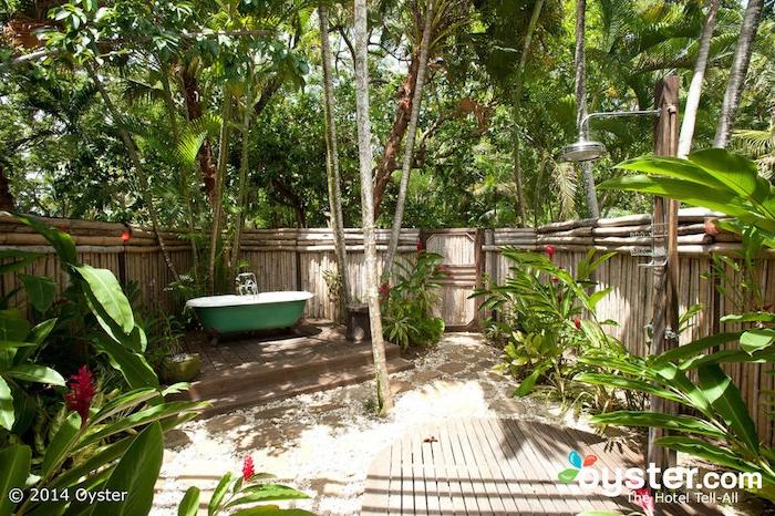 garten mit einem zaun aus vielen braunen bambus stäben, eine kleine grüne badewanne und ein sichtschutz zaun aus holz und sichtschutz pflanzen