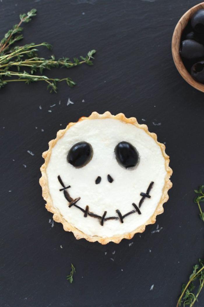 ein Kopf von Strohpuppe aus Cupcake, kleine Augen aus Bonbons und Schokolade Mund. Halloween Menü
