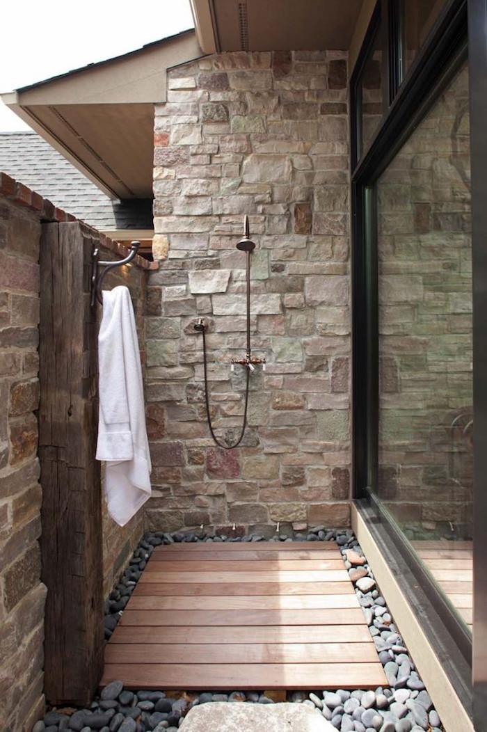 boden aus holz und vielen kleinen grauen steinen, ei haus mit terrasse mit einem weißen tuch und einer gartendusche edelstahl