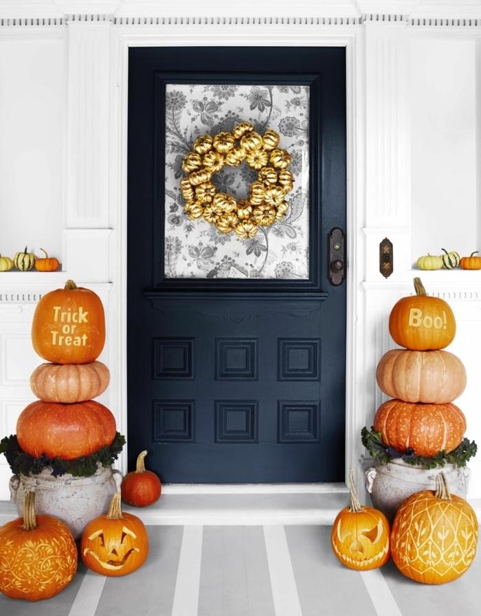 Kranz aus kleinen Deko Kürbissen an der Eingangstür, Dekoration aus Kürbissen in verschiedenen Größen und Formen