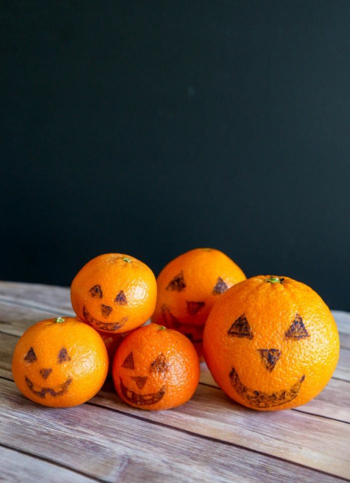 Mandarinen mit gruseligen Gesichtern, stellen Kürbisse dar, gesundes Halloween Menü