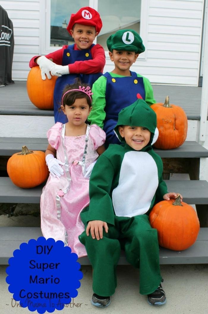 vier Kinder, die wie Helden aus Supermario maskiert sind, sitzen auf der Treppe, Kürbisse als Dekoration