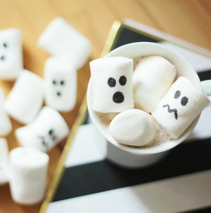 Marschmellows mit gruseligen Gesichter, in einem Becher voller Heißschokolade, Halloween Menü