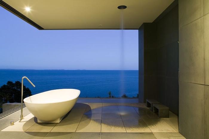 weiße badewanne und eine gartendusche edelstahl, ein haus mit einer terrasse, blaue meer und himmel