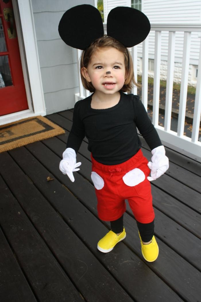 ein kleines Mädchen als Mickey Maus maskiert, rote Hosen, große schwarze Ohren und gelbe Schuhen