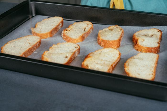 Kleine Brotscheiben auf ein mit Backpapier ausgelegtes Backblech geben und mit Olivenöl beträufeln