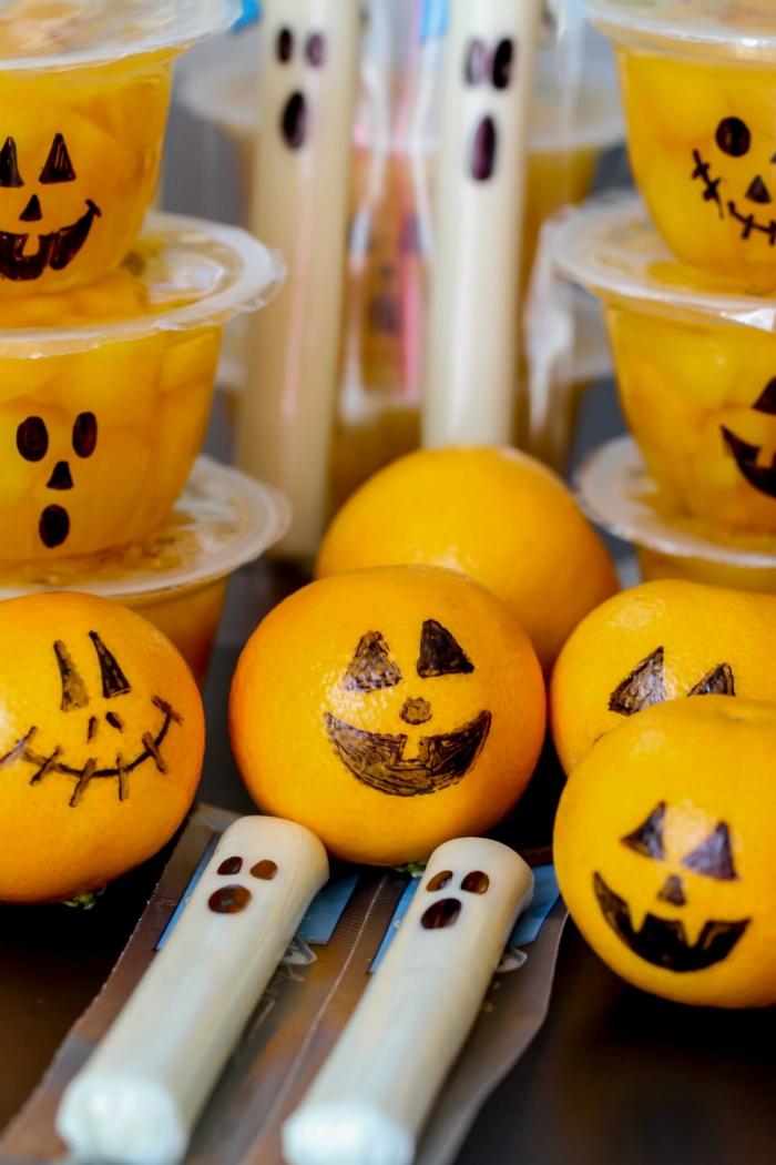 Mandarinen wie Kürbisgesichter, gesundes Halloween Menü, Kerzen in weißer Farbe auch mit Gesichter wie Gespenster