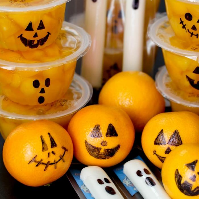 Mandarinen mit gruseligen Kürbisgesichtern, Kerzen wie Gespenster, Halloween Menü für die Schule
