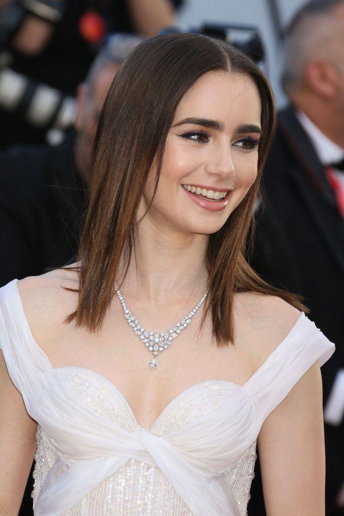 Mittellanger Haarschnitt mit Mittelscheitel, weißes Abendkleid, silberne Kette mit Kristallen, Lipgloss und Smokey Eyes