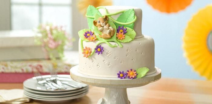 Lion King Motivtorte, Simba Figur aus Fondant, Blätter und bunte Blumen, zweistöckige Torte mit Vanillecreme
