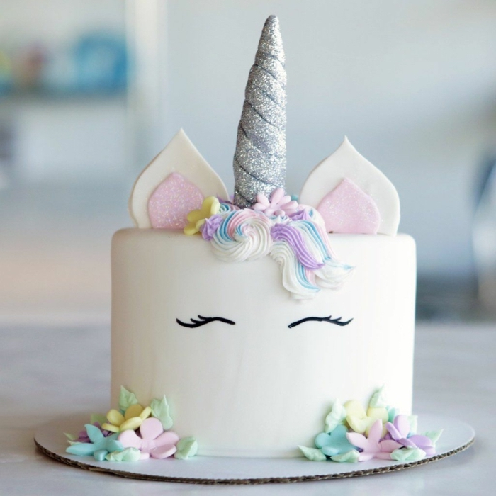 Einhorn Torte zur Taufe mit Fondant, silberner Horn, bunte Blumen und Schmetterlinge aus Zuckerguss
