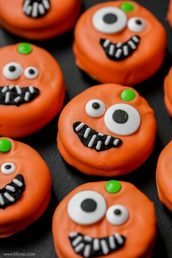 Halloween Snack Ideen, Plätzchen in oranger Farbe wie gruselige Kürbisgesichter, Augen in verschiedener Größen