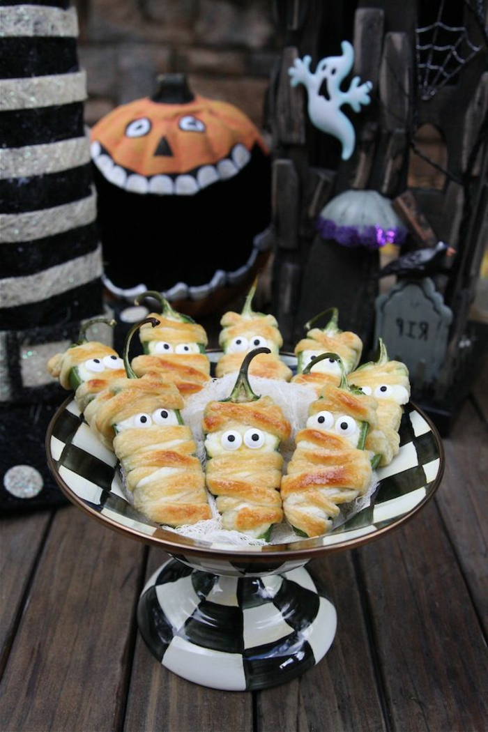 Paprikas mit Hülle aus Teig, mit weißen Augen, stellen gruselige Mumien dar, Halloween Snack Ideen