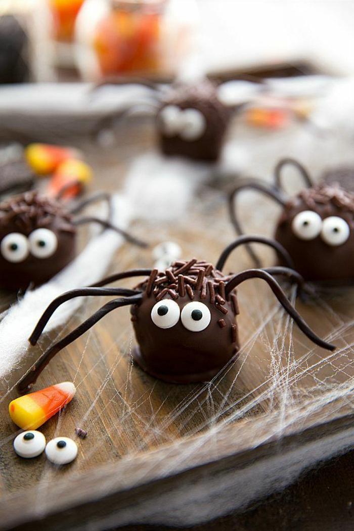 Schokolade Pralinen wie Spinnen mit weißen Bonbonaugen, Halloween Snack Ideen, Spinnennetz aus Zucker