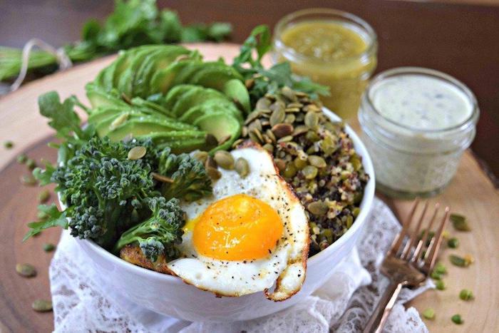 quinoa gerichte bunte kombination aus gesunden stoffen, ei, avocado, kürbissamen, kale, soßen