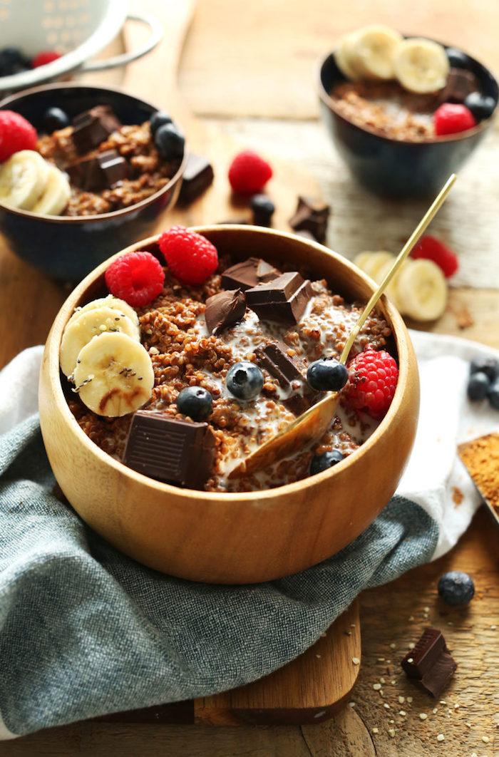 schüssel aus holz, quinoa gepufft mit schokolade, banane, himbeeren, frühstück idee