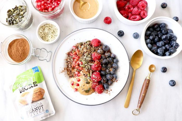 quinoa rezept einfach ideen zum frühstück, blaubeeren, himbeeren, kürbissamen, granatapfel, erdnussbutter