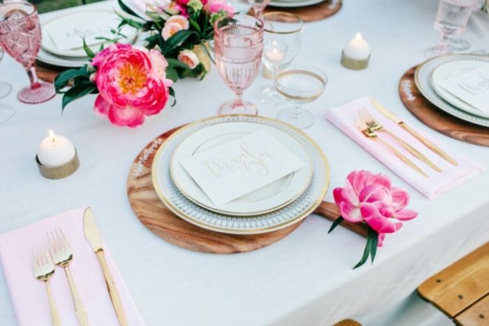 Untersilie aus Holz mit rosa Blume als Hochzeitsdekoration, rosa Serviette und goldfarbenes Besteck