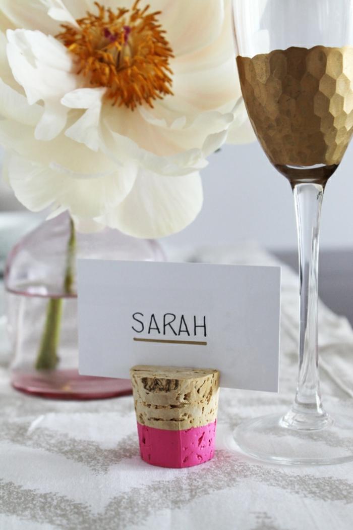 eine Korke in rosa und natürlicher Farbe, ein Weinglas, eine weiße Blume, Hochzeitsartikel