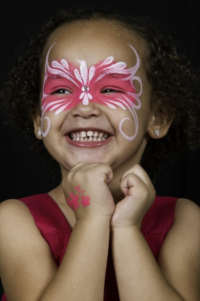 rosa Schmetterling mit weißen Konturen und Glasperle in der Mitte, Halloween Schminktipps