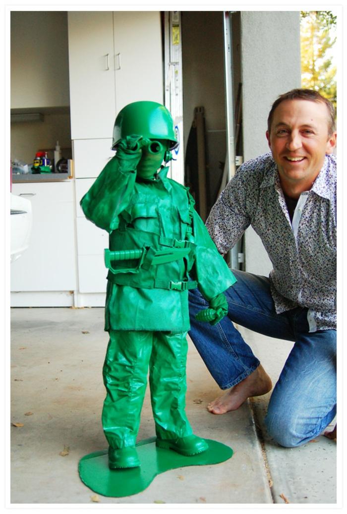 ein grüner Soldat wie das berühmte Spielzeug, Halloween Verkleidung für Junge, mit dem Vater fotografiert