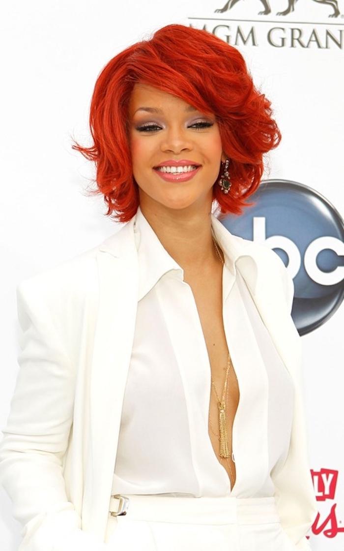 Rihanna Haarstyle, kinnlange rote Haare, weißes Outfit und lange goldene Kette, Smokey Eyes