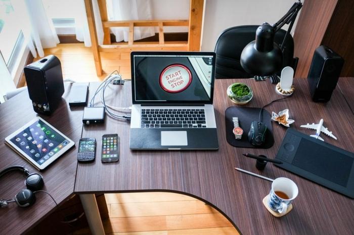 ein Schreibtisch aus Holz, mit Laptop darüber