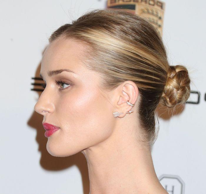 Niedriger Dutt für mittellange Haare, glatte blonde Haare, Smokey Eyes und roter Lippenstift, Ohrring in Form von Pfeil