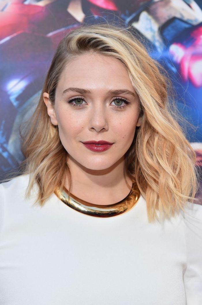 Blonde wellige Haare mit Seitenscheitel, schulterlanger Haarschnitt, schwarzer Eyeliner und roter Lippenstift