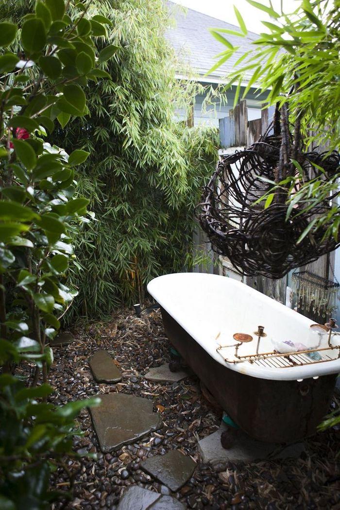 ein gartenweg mit steinen und eine wand aus vielen sichtschutz pflanzen mit grünben pflanzen, eine kleine weiße badewanne und ein haus