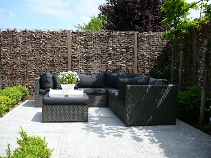graue sofas und ein grauer tisch aus rattan mit einem weißen blumentopf mit weißen blumen und grünen pflanzen und ein sichtschutz zaun aus gabionen