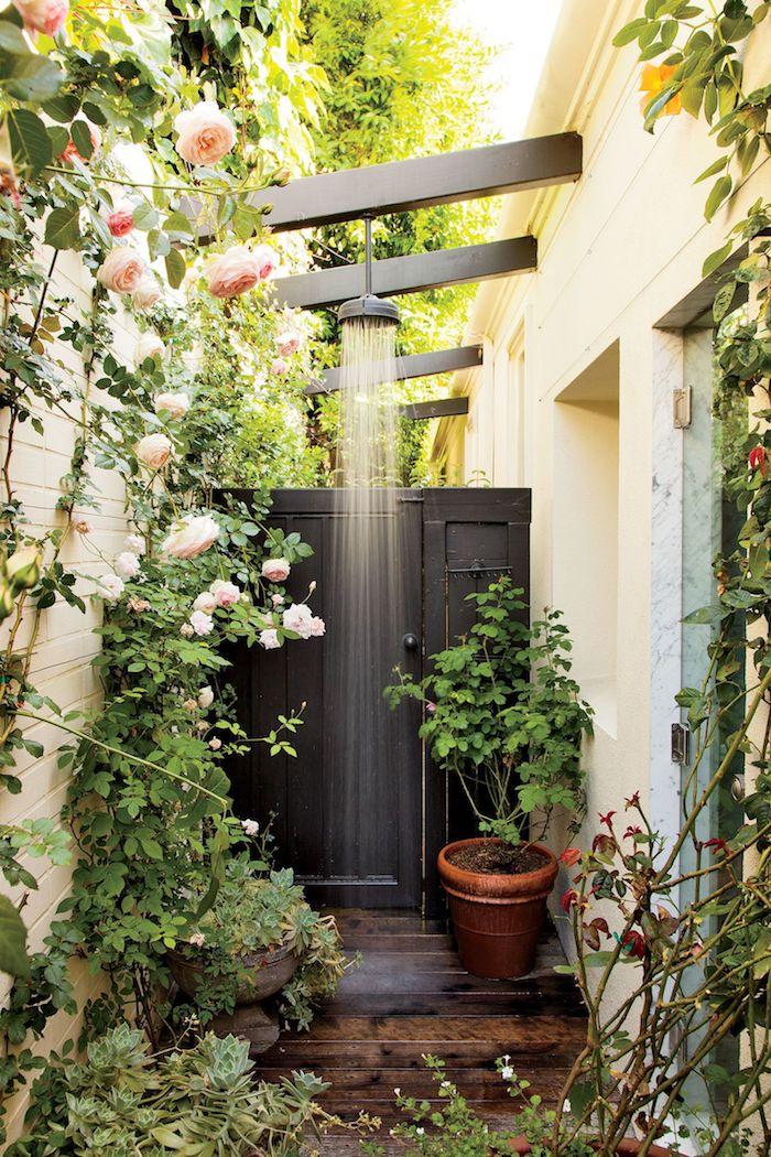 graue gartendusche in einem garten mit vielen pinken rosen und grünen blättern, sichtschitz gartendusche aus rosen