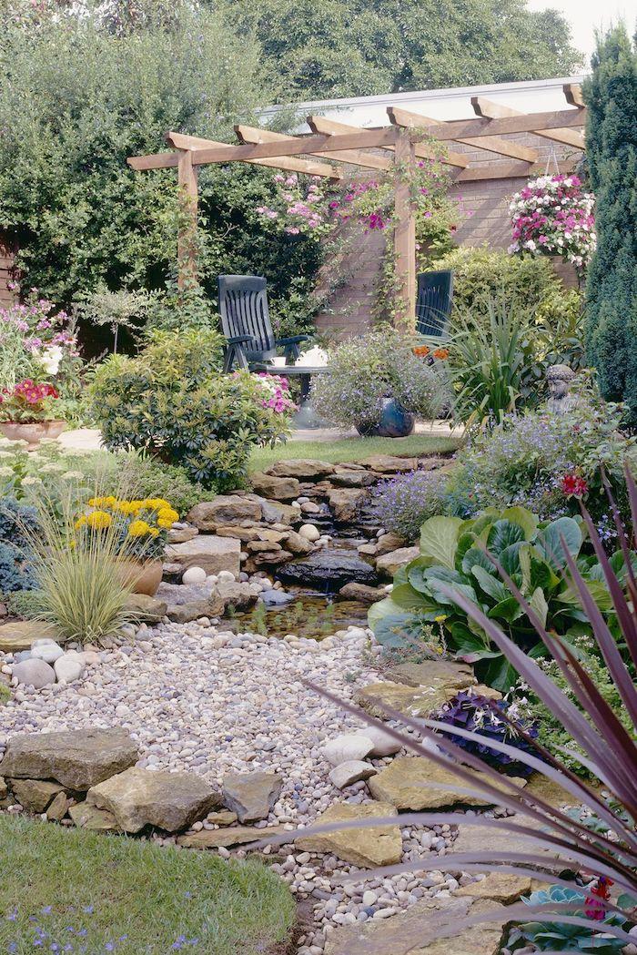 pergola im garten mit einem kleinen gartenteich und einem kleinen steingarten mit gelben und roten blumen, ein stuhl im garten