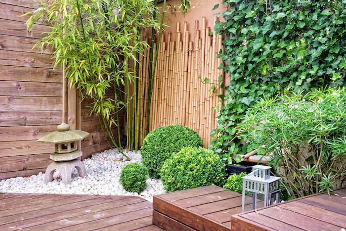 wand aus braunen bambus stäbenund ein brauner boden aus holz und weißen kleinen steinen und wand aus grünen efeu pflanzen als sichtschutz im garten