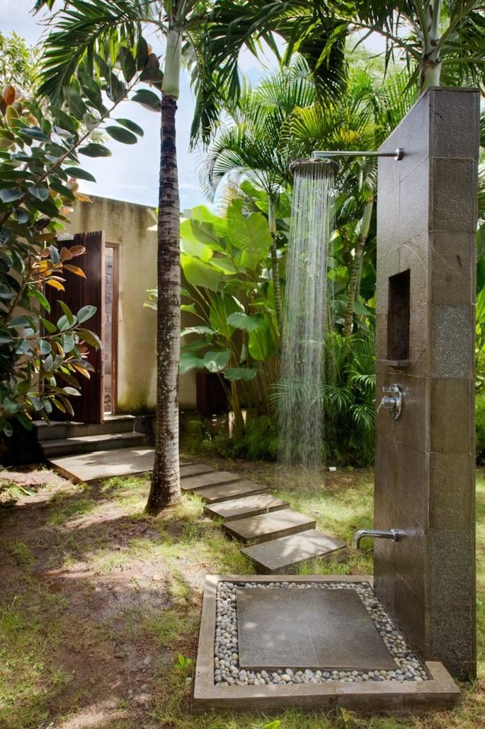 kleine gartendusche und ein gartenweg aus steinen, garten mit palmen und pflanzen mit grünen blättern, sichtschutz gartendusche bauen ideen