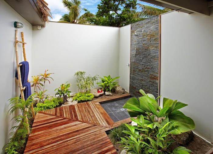 brauner boden aus holz und viele kleine grüne pflanzen mit grünen blättern, eine gartendusche und eine wand aus grauen steinen