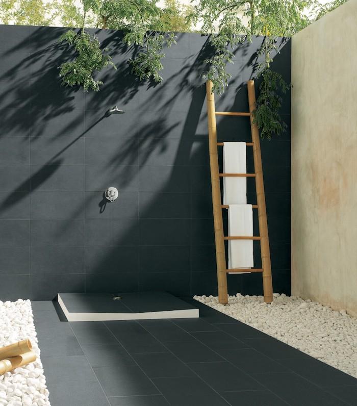 eine gartendusche selber bauen und ein sichtschutz aus einer schwarzen wand und ein boden mit vielen kleinen weißen steinen
